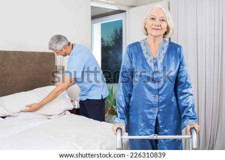 Portrait of senior woman standing with walking frame while caretaker making her bed at nursing home - stock photo