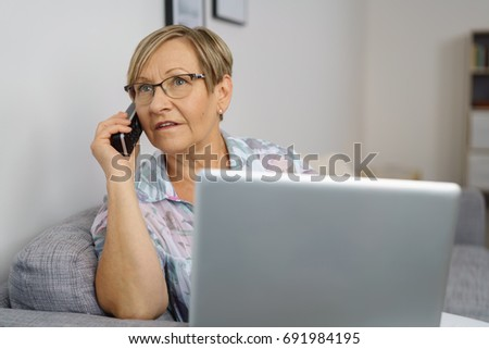 Portrait of senior woman talking on phone sitting on sofa in front of laptop