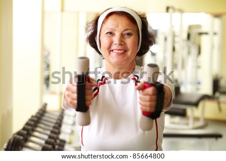 Portrait of senior woman training in gym - stock photo