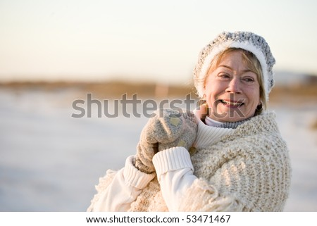 Portrait of senior woman wearing warm winter hat, sweater and gloves - stock photo