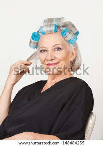 Portrait of senior woman with hair curlers against white background