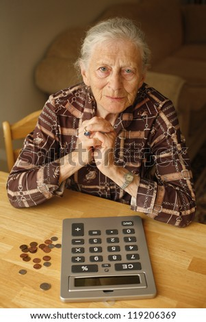 Portrait of senior woman with money and calculator - stock photo