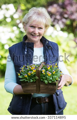 Portrait Of Senior Woman Working In Garden  - stock photo