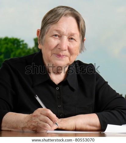 Portrait of  senior woman  writing - stock photo