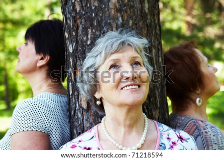Portrait of senior women standing near the tree - stock photo