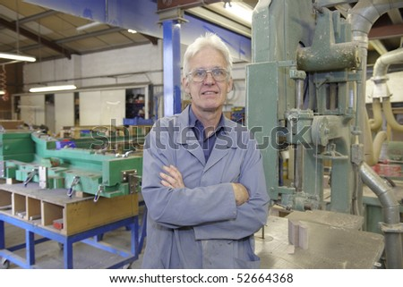portrait of senior worker on factory floor next to machine