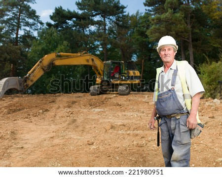 portrait of senior workman in blue uniform on construction site outdoors - stock photo