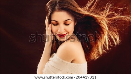 portrait of sensual beautiful young woman enjoing with passion on brown background - stock photo