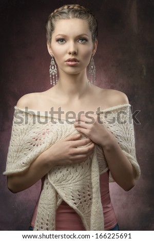portrait of sensual brunette woman with fashion elegant style, creative hair-style and precious earrings. Covering by wool shawl