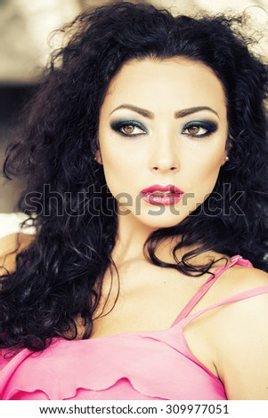 Portrait of sensual pretty young brunette woman with curly hair bright makeup expressive green brown eyes and pink lips looking away sitting outdoor, vertical picture - stock photo