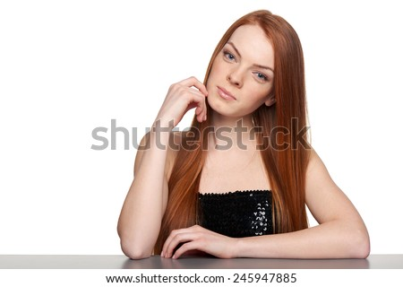 Portrait of sensual redheaded woman sitting at table leaning on elbows, over white background - stock photo