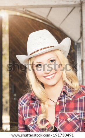 Portrait of Sensual Smiling Happy Blond Cowgirl wearing Stetson. Light Effect Used. Vertical Image - stock photo
