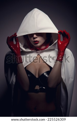 Portrait of sensual vampire girl with red lips wearing white hooded jacket, artistic shot   - stock photo