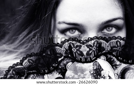 Portrait of sensual woman with seductive eyes behind fan - stock photo