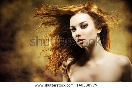 portrait of sensual young girl with brown wavy flying hair and pretty make-up looking in camera with strong color and grunge background