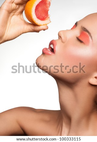 Portrait of sensual young woman with bright makeup holding delicious grapefruit in her hand - stock photo