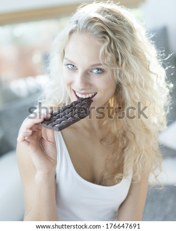Portrait of sensuous woman eating candy bar - stock photo