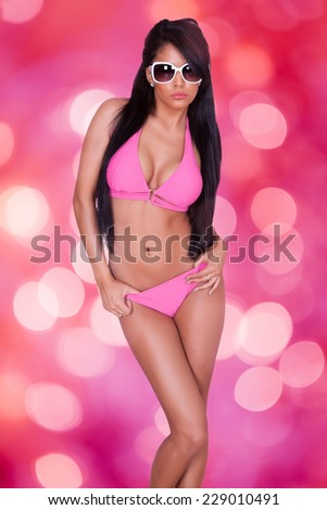 Portrait of sensuous young woman in bikini posing against pink background - stock photo