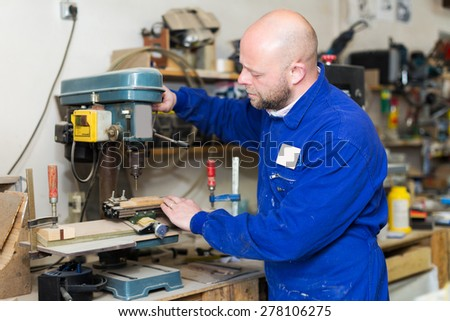 Portrait of serious adult professional woodworker on lathe at musical instrument workroom