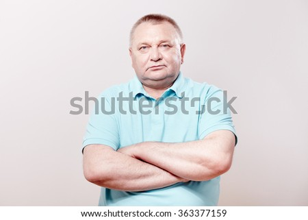 Portrait of serious aged man wearing blue shirt standing with crossed arms against white wall - retirement concept