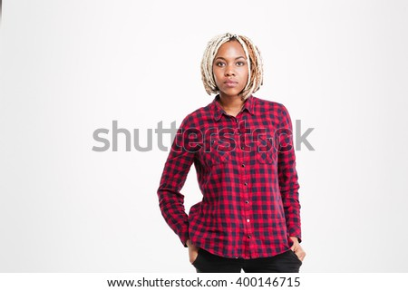 Portrait of serious beautiful young african american woman with braids in checkered shirt standing over white background - stock photo