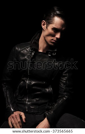portrait of serious biker in black leather jacket posing seated in dark studio background looking away - stock photo