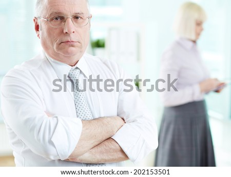 Portrait of serious boss looking at camera with female standing on background - stock photo