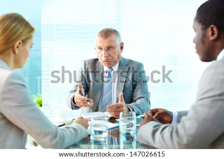Portrait of serious boss talking to his employees - stock photo