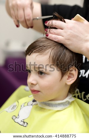 Portrait of serious boy at the barbershop - stock photo