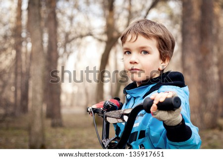 Portrait of serious boy with bicycle - stock photo