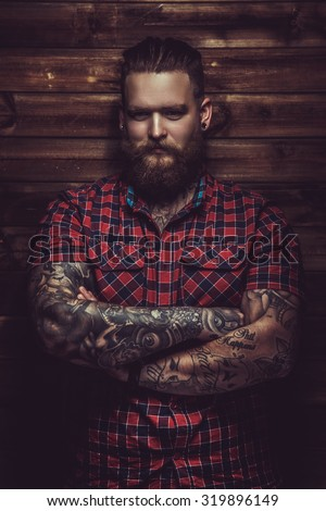 Portrait of serious brutal man with beard and tattooes. Crossed arms.