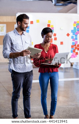 Portrait of serious business people standing and discussing in studio - stock photo