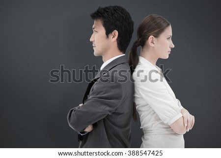 Portrait of serious business people standing back-to-back against grey background - stock photo