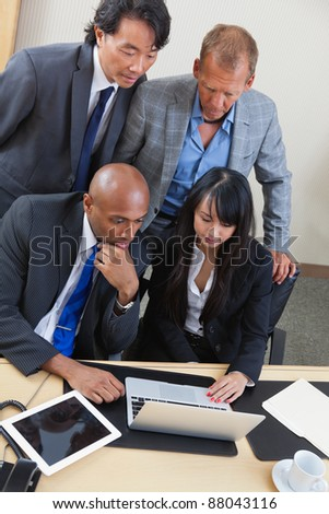 Portrait of serious business team working on laptop together - stock photo