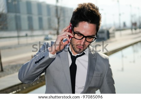 Portrait of serious businessman in urban background talking on phone - stock photo