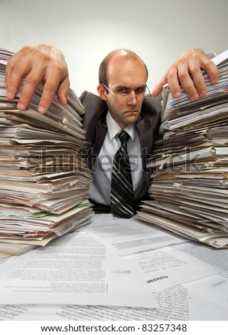 Portrait of serious businessman with big piles of paperwork - stock photo
