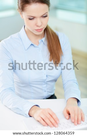Portrait of serious businesswoman typing at workplace - stock photo