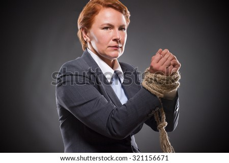 Portrait of serious businesswoman with her hands tied up. Lady in grey business suit having her hands tied up with strong rope.