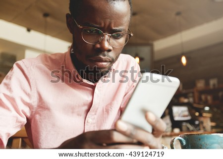 Portrait of serious busy African entrepreneur in shirt and glasses, using mobile phone for business correspondence, looking at the screen with concentrated face. Selective focus on the cell phone - stock photo