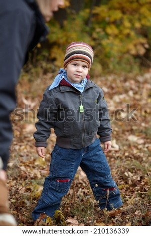 Portrait of serious casual little kid standing at outdoor park wearing warm clothes. Looking at camera, - stock photo