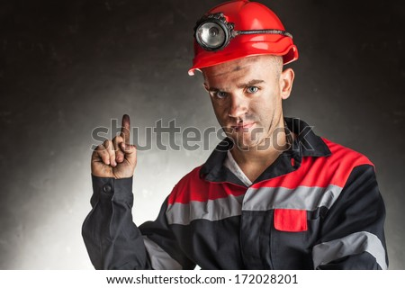 Portrait of serious coal miner with good idea holds finger up against a dark background - stock photo