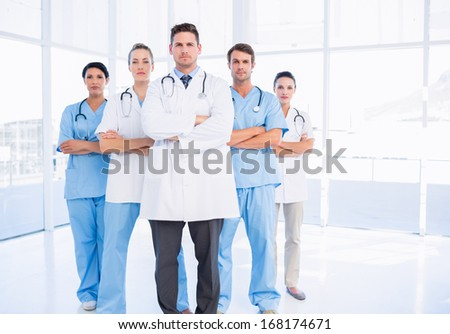 Portrait of serious confident group of doctors standing at the medical office - stock photo
