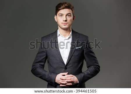 Portrait of serious confident young businessman in black suit and white shirt over grey background - stock photo
