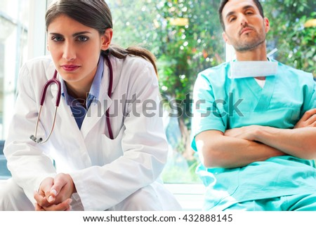 Portrait of serious female doctor with colleague in hospital. Young medical professionals are in uniforms. They are sitting in clinic.