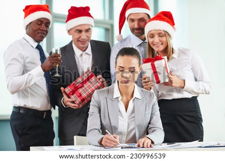 Portrait of serious female employee analyzing document with group of colleagues preparing her Christmas surprise - stock photo
