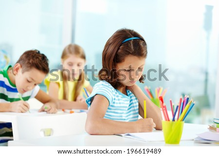 Portrait of serious girl drawing at workplace with her schoolmates on background - stock photo