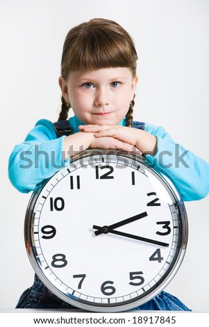 Portrait of serious girl with clock looking at camera