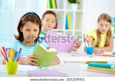 Portrait of serious girl with notepad reading notes on background of her classmates
