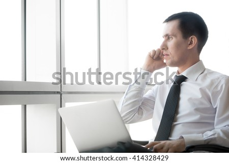 Portrait of serious handsome young business man working on laptop computer and making call. Caucasian businessperson in formal wear during his workday. Office worker talking on phone. Copyspace. - stock photo