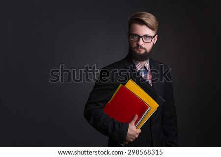 Portrait of serious hipster bearded businessman with documents. Boss in glasses posing in black business suit on dark background. - stock photo